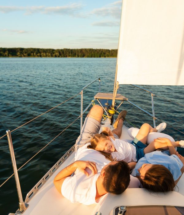 Family Lying On Yacht Deck Relaxing On Sailboat Ride