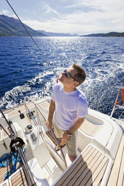 Happy skipper driving sailboat.