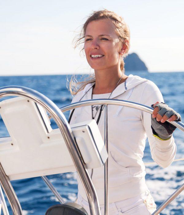 Female skipper sailing on yacht, copy space